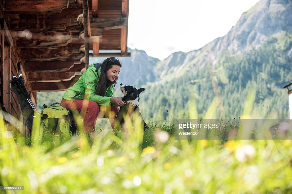 Austria, Altenmarkt-Zauchensee, young woman with dog at alpine cabin