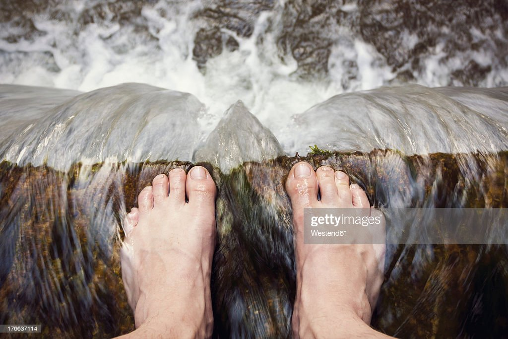 Austria, Barefooted man standing at edge of waterfall
