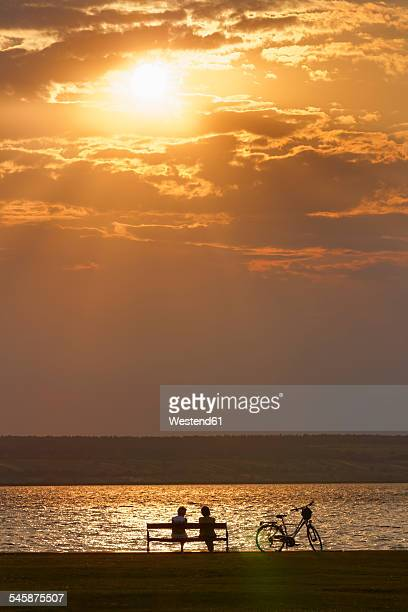 Austria, Burgenland, Illmitz, Lake Neusiedl, People sitting on bench at sunset