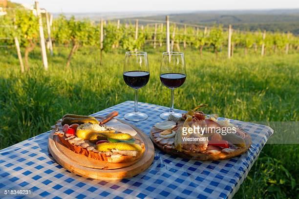 Austria, Burgenland, Oberwart District, Eisenberg an der Pinka, Red wine glasses, Caraway roast and vintner-plate on table