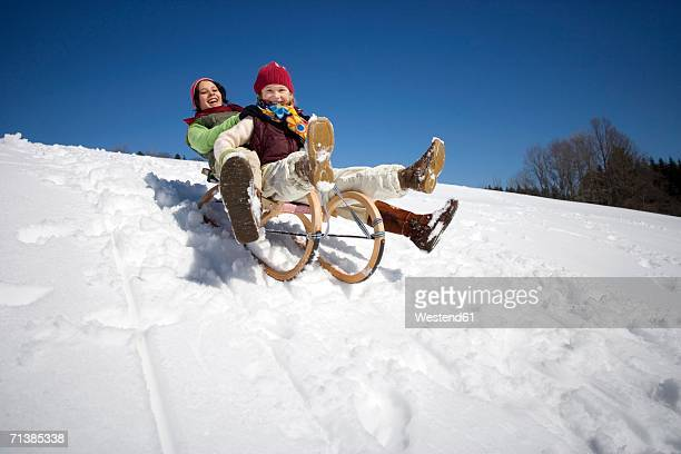 Austria, girls (6-17) sledging on snow covered slope, smiling, low angle view