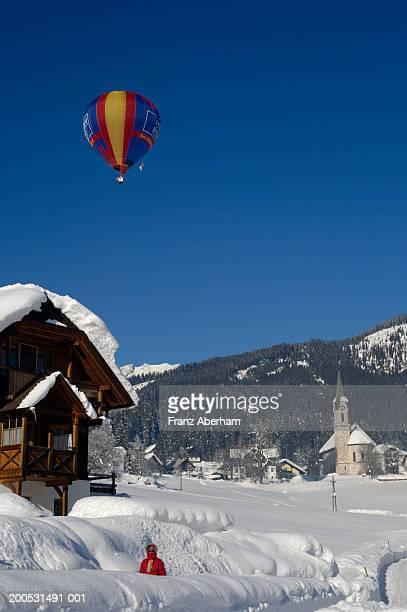 Austria, Gosau, hot air balloon above village covered in snow, winter