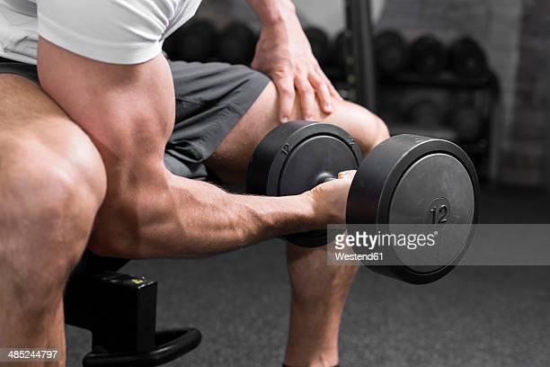 Austria, Klagenfurt, Man in fitness center training with dumbbell