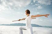 Austria, Kranzhorn, Mid adult woman exercising stick fighting on mountain top