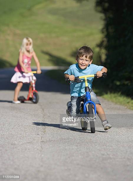 Austria, Mondsee, Girl and boy (2-5) riding bicycle