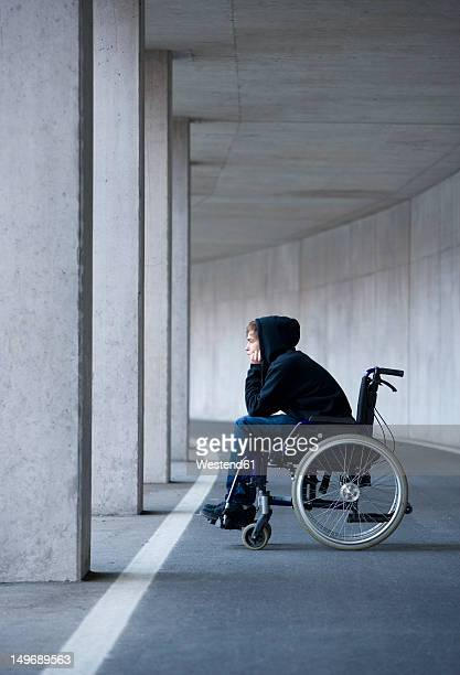 Austria, Mondsee, Young man sitting on wheelchair at subway