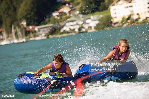 Austria, Moon Lake, Teenage boy and girl (14-17) riding water sled