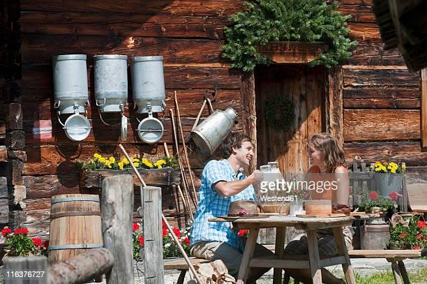 Austria, Salzburg Country, Altenmarkt-Zauchensee, Couple sitting outside of farmhouse on mountains of Niedere Tauern