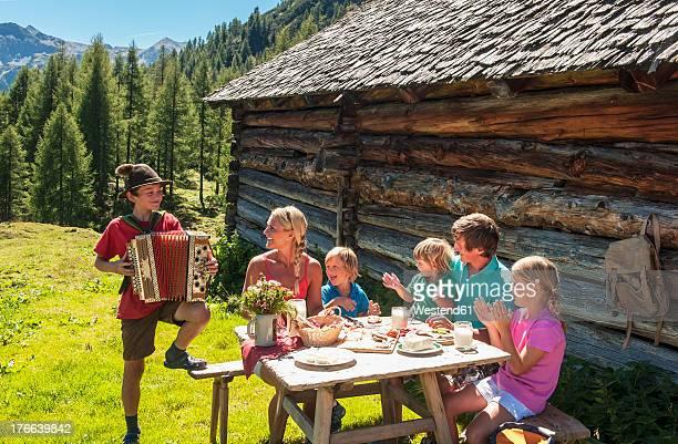 Austria, Salzburg Country, Family sitting outdoors enjoying boy playing accordion