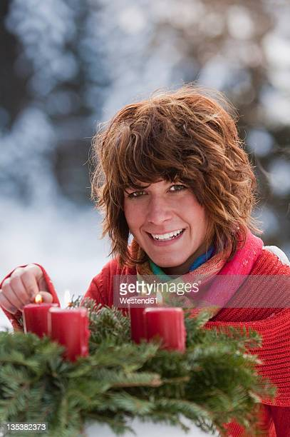Austria, Salzburg Country, Flachau, Close up of young woman igniting candles of advent wreath in winter