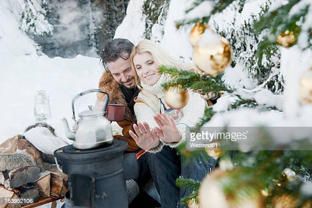 Austria, Salzburg County, Couple sitting near camping stove and drinking tea