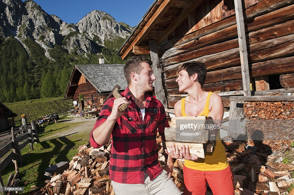 Austria, Salzburg County, Man and woman with chopped wood, smiling : Stock Photo