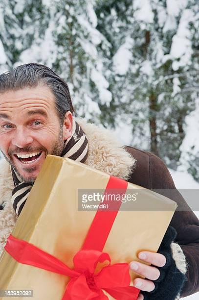 Austria, Salzburg County, Mature man standing with christmas parcel, smiling, portrait