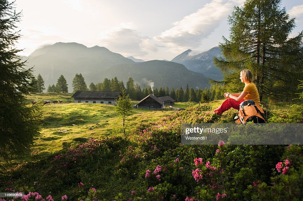 Austria, Salzburg County, Young woman sitting in alpine meadow and watching landscape