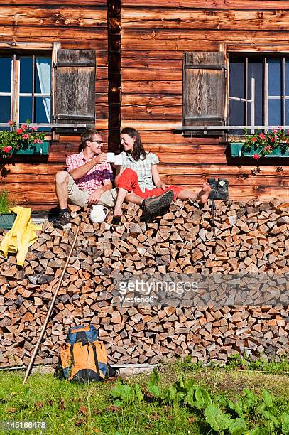 Austria, Salzburg, Couple sitting on logs by hut