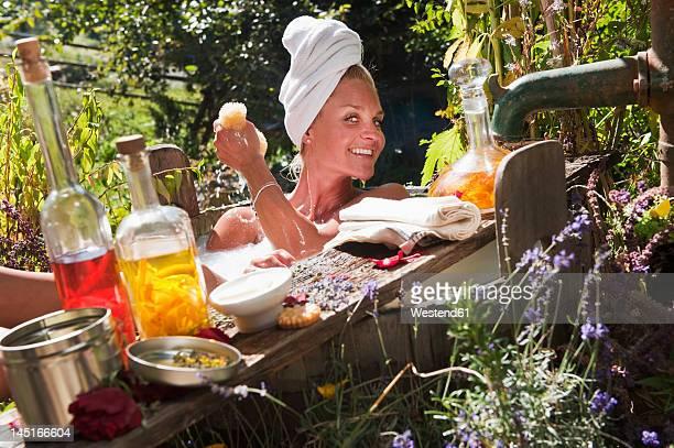 Austria, Salzburg, Flachau, Young woman taking milkbath in tun