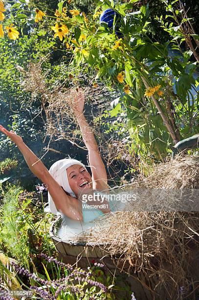 Austria, Salzburg, Flachau, Young woman taking milkbath with hay in tun
