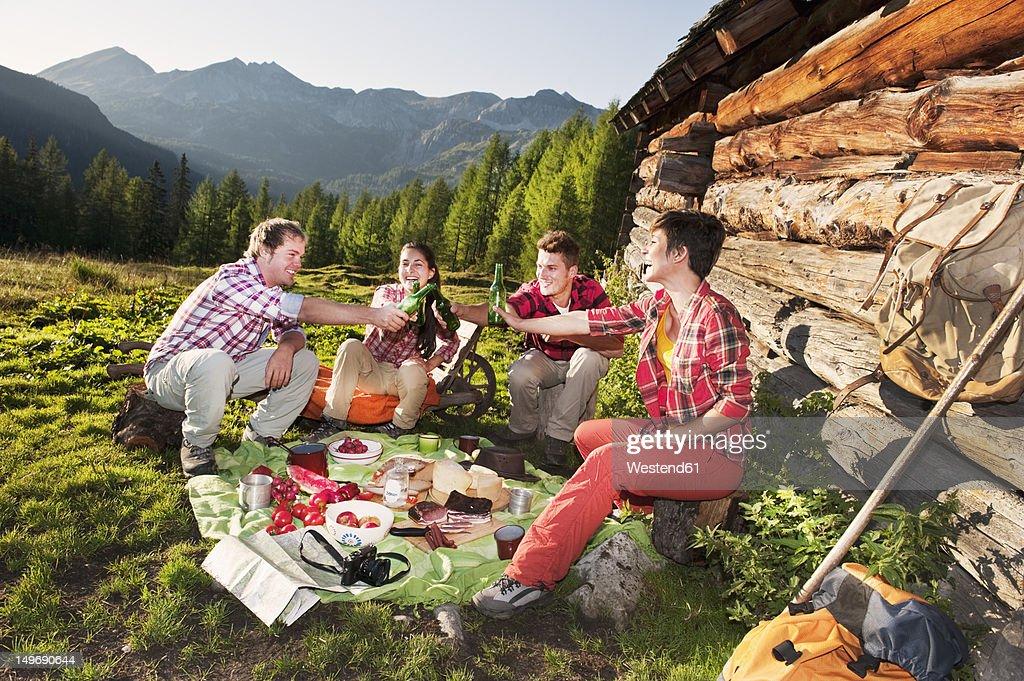 Austria, Salzburg, Men and women having picnic near alpine hut at sunset