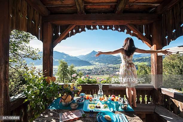 Austria, Salzburg State, Altenmarkt-Zauchense, woman enjoying view from veranda of old farmhouse