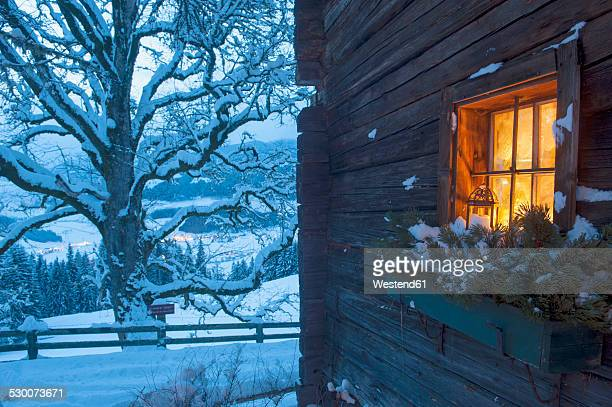 Austria, Salzburg State, Altenmarkt-Zauchensee, facade of wooden cabin with lightened window in winter