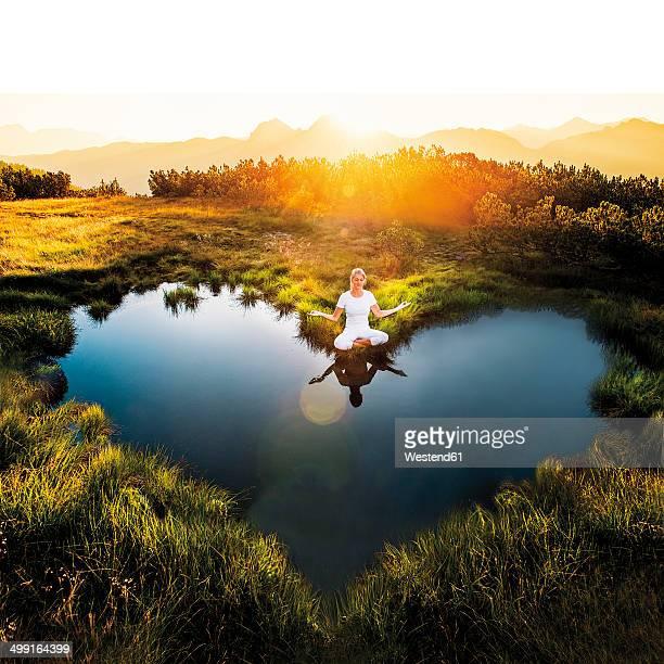 Austria, Salzburg State, Altenmarkt-Zauchensee, meditating woman at pond