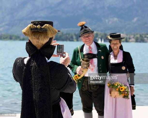 Austria, Salzburg, Woman taking photography of senior couple