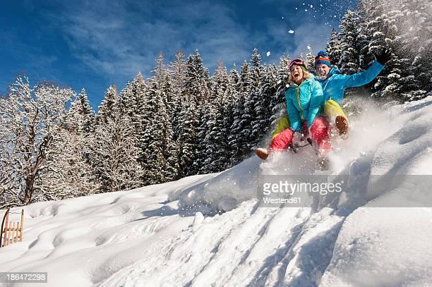 Austria, Salzburg, Young man and woman with sledge in snow at Altenmarkt Zauchensee