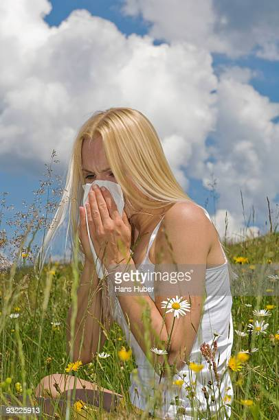 Austria, Salzburger Land, Altenmarkt, Young woman sneezing in meadow
