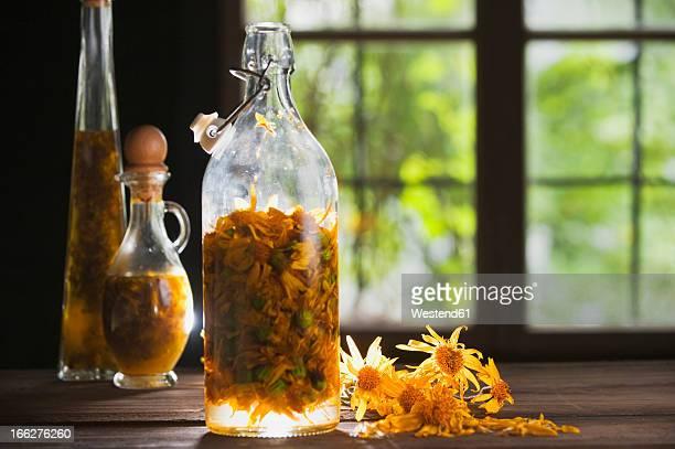 Austria, Salzburger Land, Arnica flower preserved in bottle on table