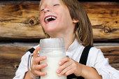 Austria, Salzburger Land, Boy (6-7) drinking milk, laughing, portrait