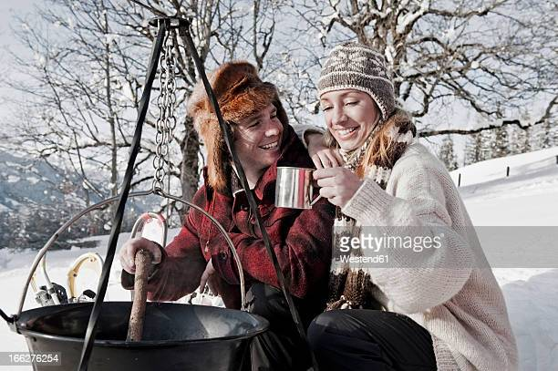 Austria, Salzburger Land, Couple cooking on campfire