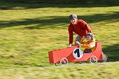 Austria, Salzburger Land, Man pushing soapbox car, boy (12-13) steering
