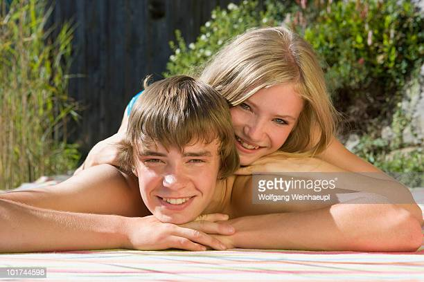 Austria, Salzburger Land, Teenagers (14-15) lying in garden, smiling, portrait
