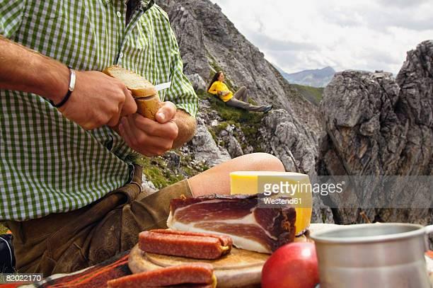 Austria, Salzburger Land, young couple having picnic on mountain, man cutting bread