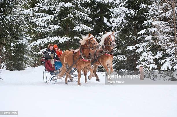 Austria, Salzburger Land, Young couple riding sleigh on snow