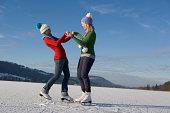 Austria, Salzkammergut, Lake Irrsee, Two teenage girls (14-15) skating and dancing