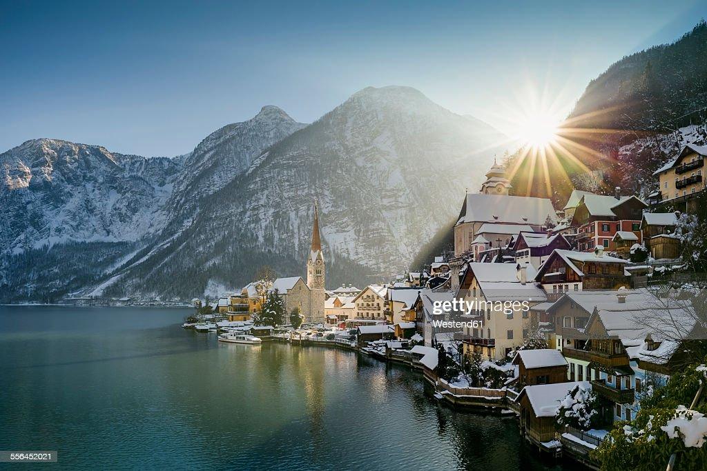 Austria, Salzkammergut, view of Hallstatt and Dachstein over lake Hallstaetter See at sunrise in winter