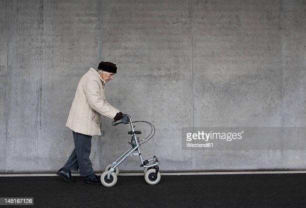 Austria,  Senior woman with wheeled walker at Subway