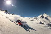 Austria, Skier doing turn in fresh powder snow