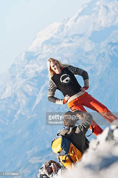 Austria, Steiermark, Dachstein, Man taking photograph of woman on mountain  top