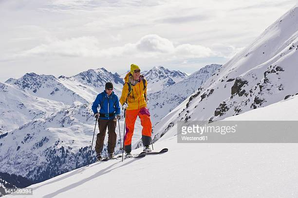 Austria, Stuben, Young couple doing telemark skiing on arlberg mountain