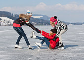 Austria, Teenage girl fallen on ice rink and friends helping her