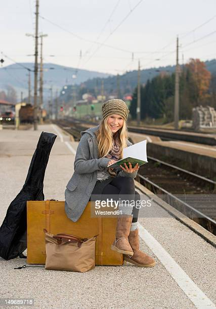 Austria, Teenage girl with suitcase on train station