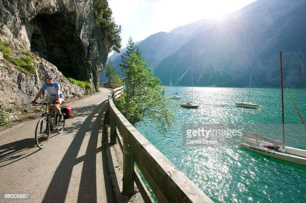 Austria, Tyrol, Achensee, woman mountain biking lakeside