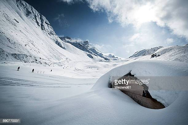 Austria, Tyrol, Ischgl, snow-capped hut in winter landscape