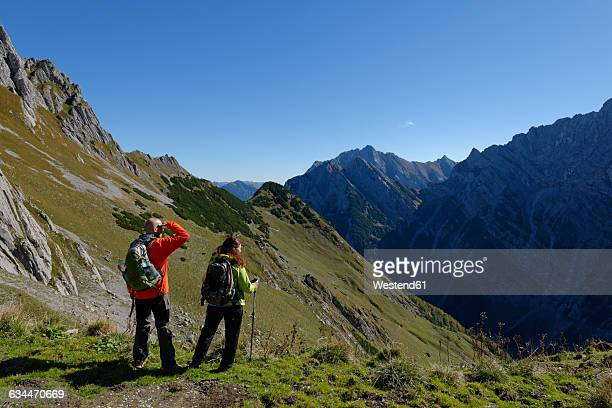 Austria, Tyrol, Karwendel, hikers looking at view at the Torscharte