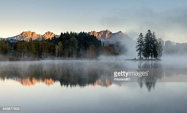 Austria, Tyrol, Kitzbuehl, view to Schwarzsee with morning mist and Kitzbuehel Alps in the background