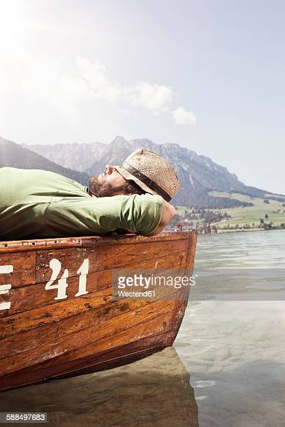 Austria, Tyrol, man relaxing on a boat on Walchsee