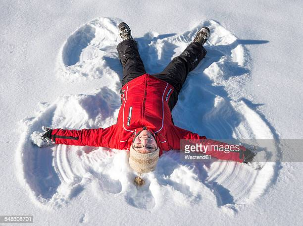 Austria, Tyrol, Pertisau, young woman making snow angel