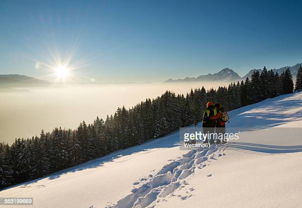 Austria, Tyrol, Schwaz, couple with snowshoes looking at view